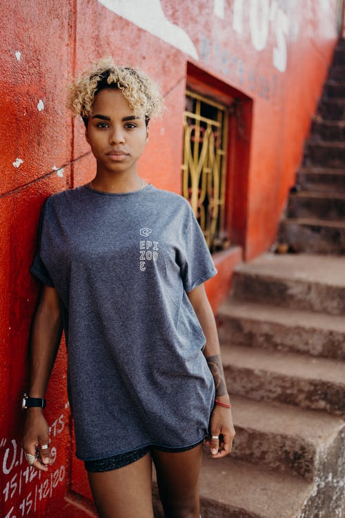 Boy in Blue Crew Neck T-shirt Standing Beside Red Concrete Wall