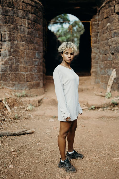 Woman in White Long Sleeve Shirt Standing on Brown Soil