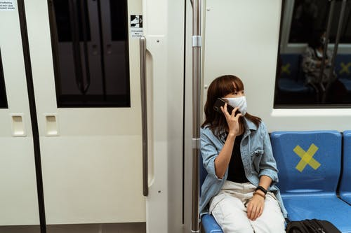 Woman Wearing a Face Mask and Talking on her Smartphone