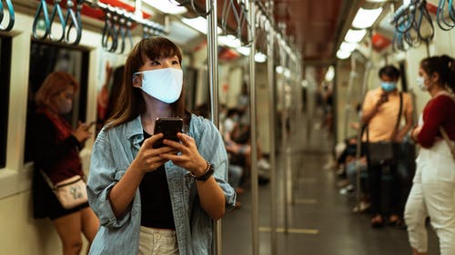 Woman Wearing a Face Mask on the Subway and Using her Smartphone