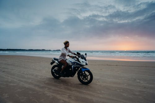 Man and Woman Riding Motorcycle on Beach
