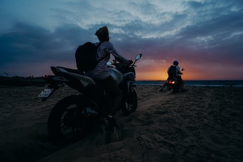 Man and Woman Riding Motorcycle on Beach during Sunset