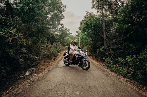 Man in Brown Jacket Riding Motorcycle on Dirt Road