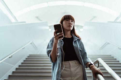 Serious woman using smartphone on stairs