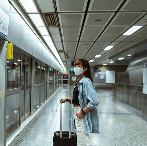Woman Wearing a Face Mask and Holding her Luggage