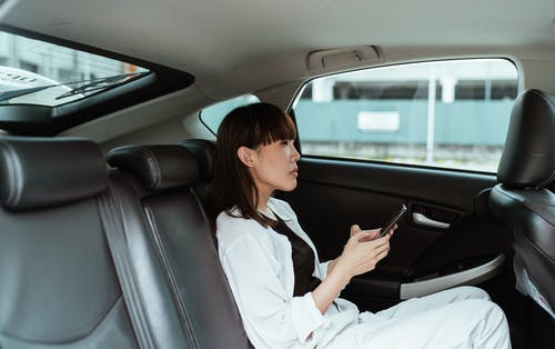 Side view of focused young Asian female wearing casual white clothes and using modern smartphone while riding at car backseat