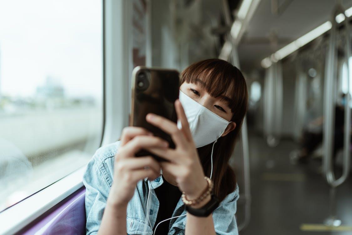 Mulher Usando Uma Máscara Facial E Segurando Um Smartphone