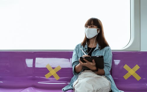 Woman Wearing a Face Mask and Using a Tablet