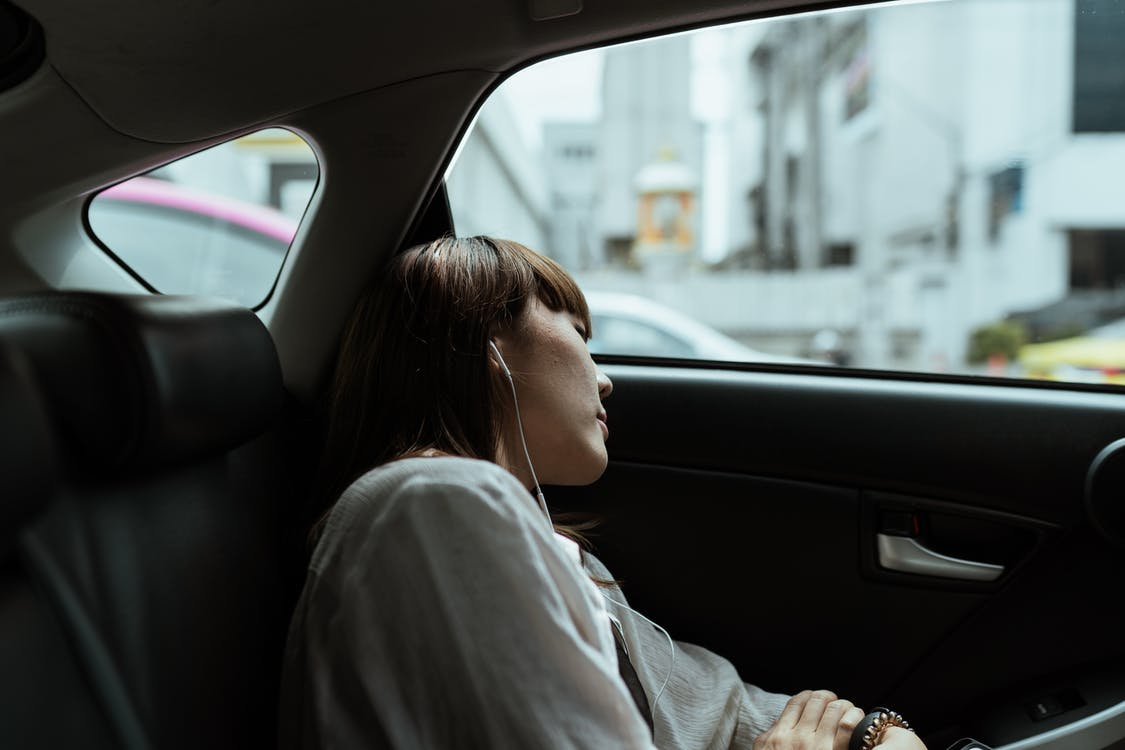 Side view of unemotional female in white shirt resting in car passenger seat and listening to music via earphones while riding in urban environment
