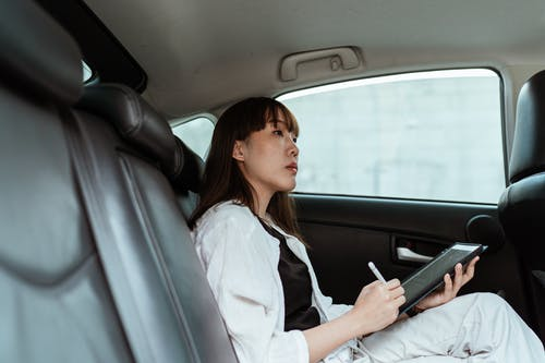 From below side view of contemplative Asian lady  in black and white outfit sitting in car passenger seat and working on tablet with stylus