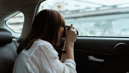 Woman taking photo on photo camera from car backseat