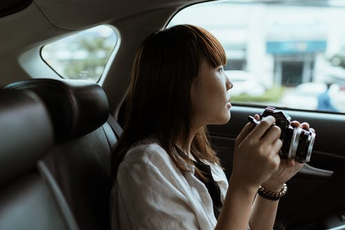 Side view of calm Asian female in casual wear with professional photo camera sitting on comfortable car backseat and looking out window pensively
