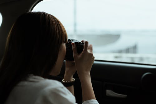 From behind anonymous brunette in white shirt taking pictures of urban buildings while riding in car passenger seat on daytime