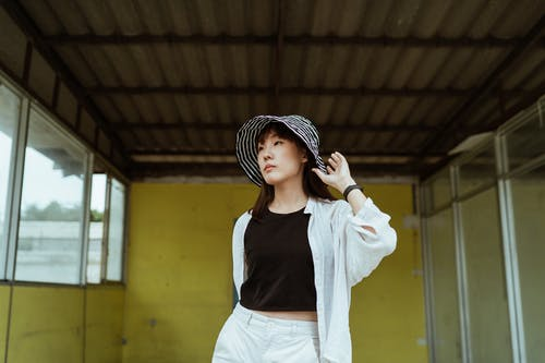 Content young Asian female in trendy wear and cool striped hat standing against yellow weathered wall in old building and looking away thoughtfully while touching hat