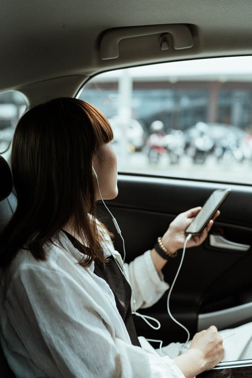 Woman using smartphone and listening to music via earphones