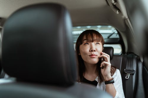 Smiling Asian lady talking on smartphone in car