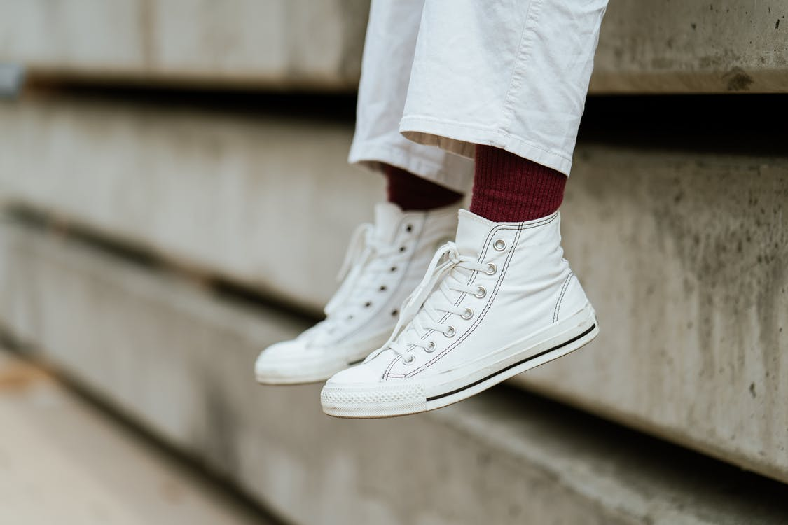 Crop unrecognizable person in stylish sneakers sitting on concrete beam