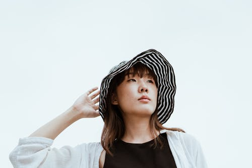 Dreamy Asian woman in hat touching head on blue background