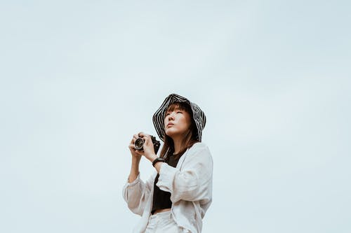 From below of young Asian female in striped hat and stylish wear looking away while standing with digital photo camera near blue wall