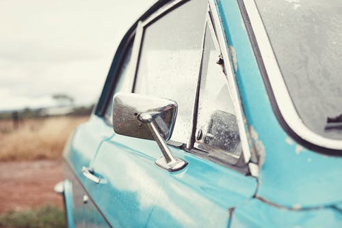 Old blue retro car after rain parked in countryside against cloudy sky in overcast weather