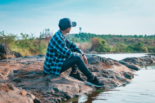 Faceless young man in cap sitting by water against amazing natural scenery