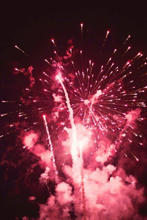 Bright firework with smoke cloud in dark sky at night