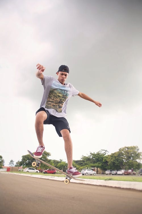 From below of fit male athlete jumping with skateboard above asphalt roadway under cloudy sky in city