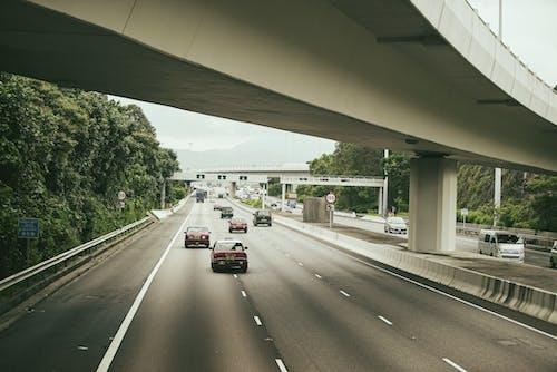 Cars driving on road under city bridge