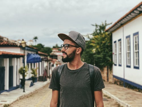 Dreamy ethnic tourist on pathway between old houses
