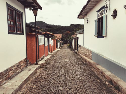 Rough narrow walkway between aged buildings near mountain under cloudy sky in city