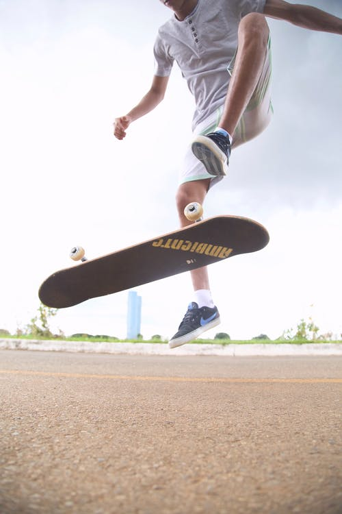 From below of crop unrecognizable sportsman performing trick on skateboard above road in city