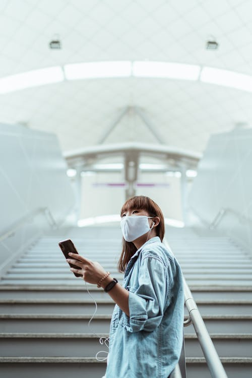 Woman With a Face Mask Holding her Smartphone