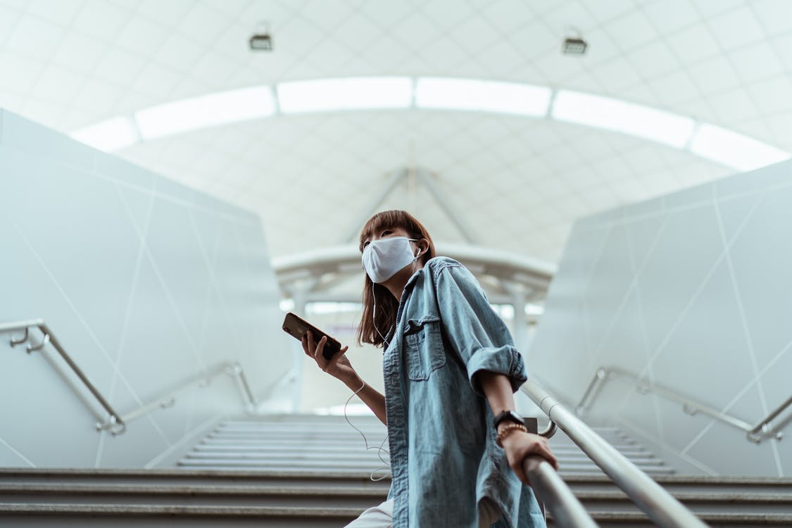 Woman With a Face Mask Holding a Handrail