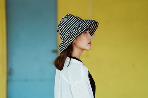 Pensive woman in striped hat standing near yellow wall