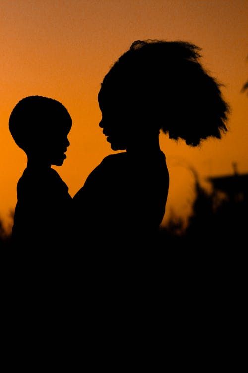 Silhouette Photo of Mom and Child Against Orange Background
