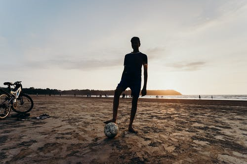 Silhouette of Man Playing Soccer on Beach during Sunset