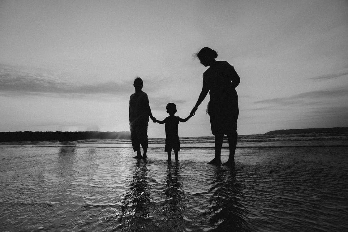 Monochrome Photo of People Holding Hands While Standing on Beach