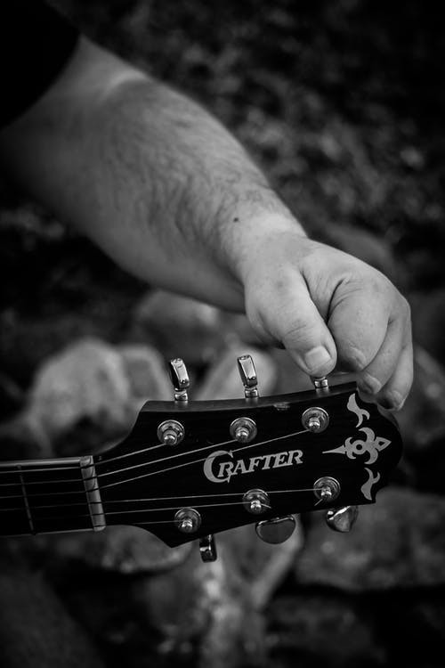 Grayscale Photo of Person Tuning His Guitar