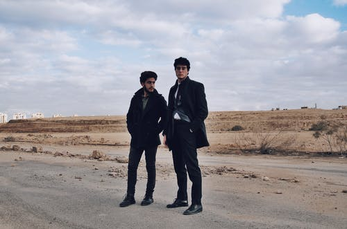 Stylish ethnic men on shabby road under cloudy sky