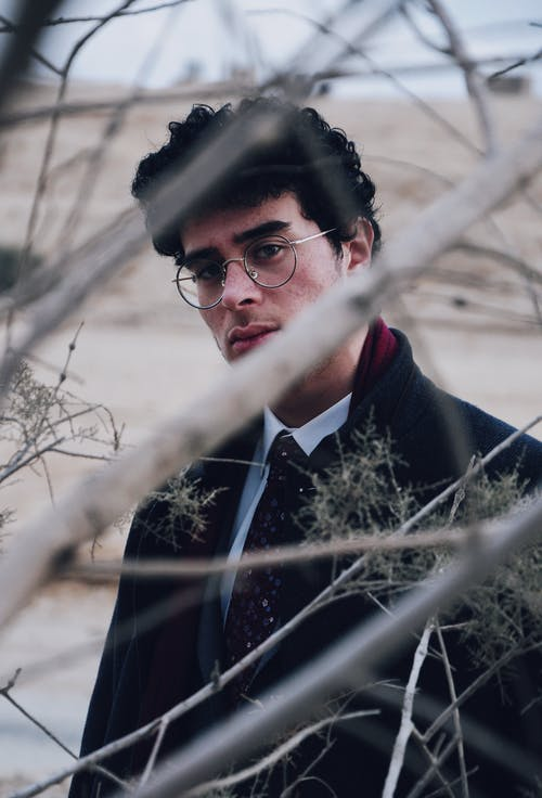 Ethnic man in eyeglasses and stylish wear near dry tree