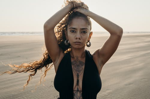 Woman in Black Halter Top and Black Vest Standing on Beach