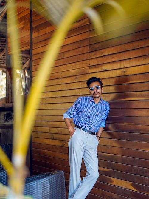 Man in Blue Dress Shirt and Beige Pants Standing on Wooden Floor