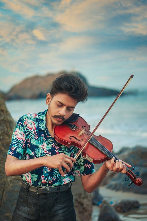 Man in Blue White and Red Floral Button Up Shirt Playing Violin