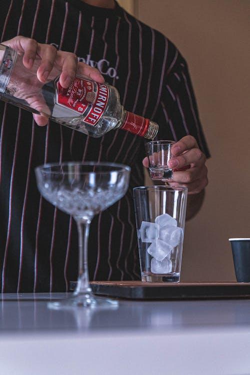 Crop barman preparing alcoholic cocktail in bar
