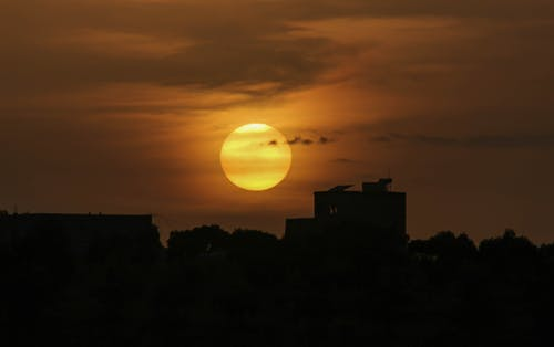 Bright sun in sky over silhouettes of city houses