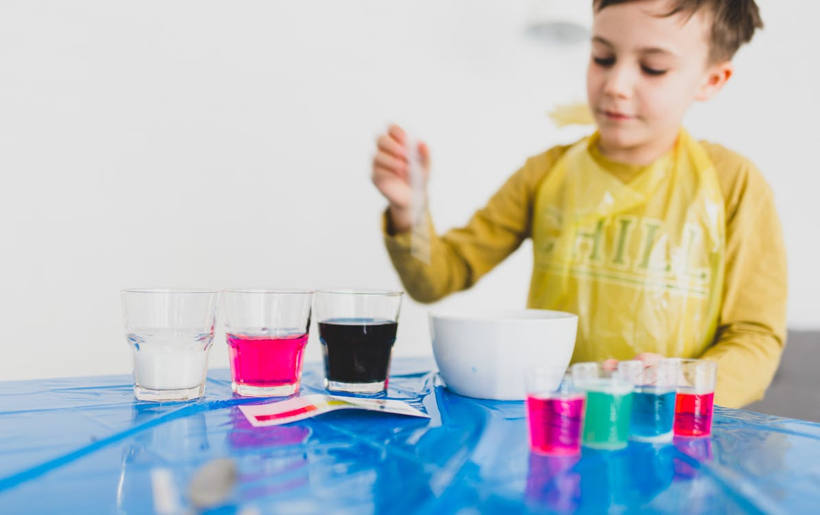 Boy mixing colorful liquids placed on table