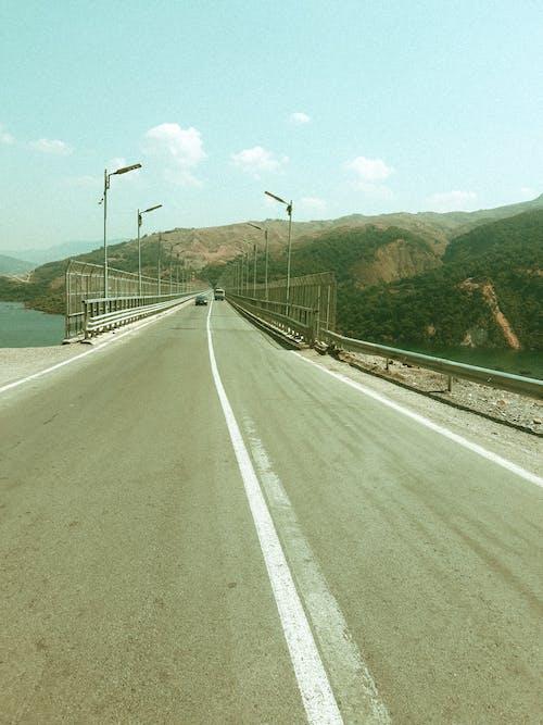 Gray Concrete Road Near Body of Water