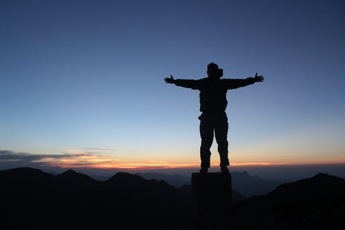 Anonymous male climber standing on mountain top with outstretched arms at sundown