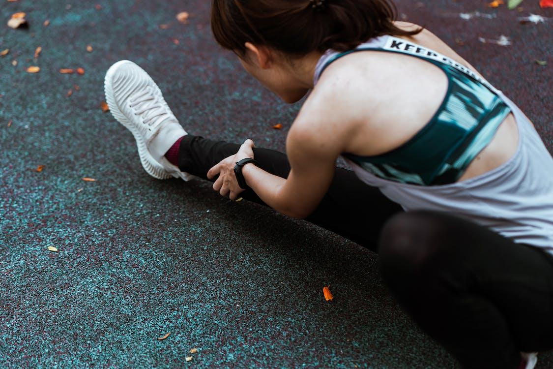 Crop faceless sportswoman stretching legs on asphalt road in autumn