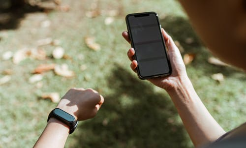 Crop anonymous woman in smart watch surfing internet on smartphone